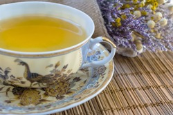 A cup of tea with a beautiful vintage bouquet of dried flowers on wicker cloth. Horizontal view