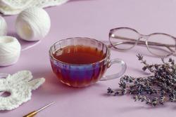 A cup of tea with a saucer, lavender branches, needlework made of white yarn, close-up-the concept of needlework for the elderly