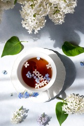 A cup of tea with flowers. Summer background. A bouquet of lilacs on the table. Romantic breakfast.