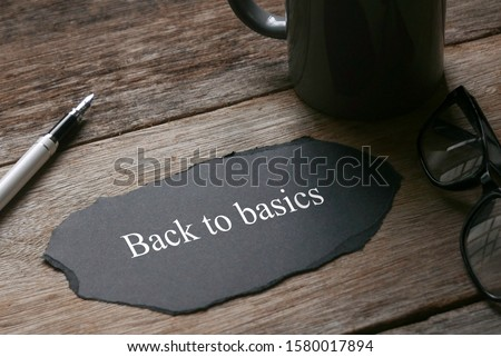 A cup,pen,glasses and a piece of black paper written with Back to basics on wooden background.