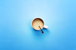 A Cup with coffee and spoon on a colored background. The concept of coffee breaks