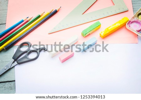 a cup with colored pencils, watercolor paints, a notebook, a ruler, a stapler, scissors on a blue wooden background, top-down view