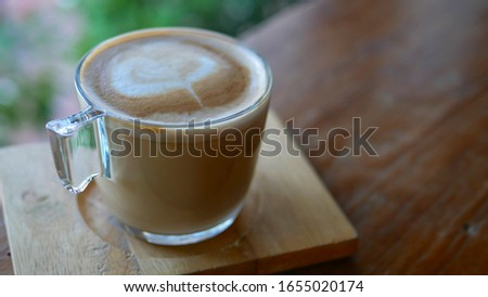 A Cups of cappuccino with latte art on wooden background. Beautiful foam, Place for text, Drinks concept.