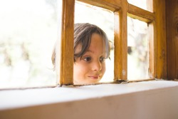 A curious boy looks out the window, A child peeps into the house through the window, Playful kid, Portrait of a brown-eyed child, Observation through the window, the emotions of a child.