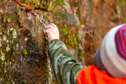 A curious caucasian boy wearing winter clothes is reaching out to a piece of icicle that formed over a tiny stick on side of a mossy rock. This is a cold day in forest.