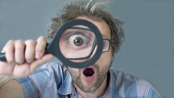 a curious funny surprised Middle-aged  man who is looking at the camera through a magnifying glass. Humorous portrait of a crazy man with no cut hair.