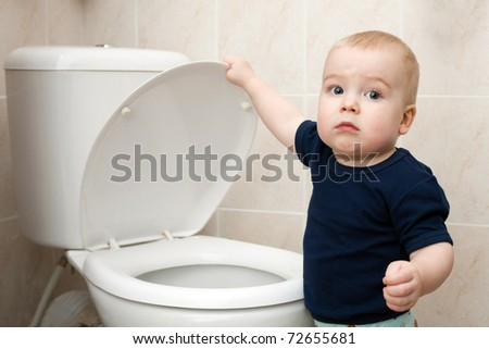 a curious little boy looks in the toilet