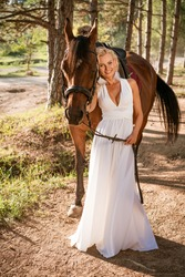 A curly blonde girl, dressed in a white dress to the floor, holds a horse near herself against the backdrop of the forest. Photo concept.