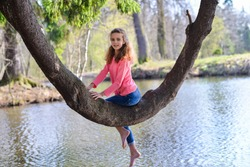 A curly-haired, long-haired girl of European appearance in a pink jacket and blue jeans, sitting barefoot on an unusually crooked tree above the lake
