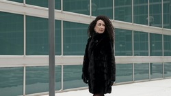 a curly-haired stylish middle-aged brunette woman in a black fur coat walking alone in the city on a cold day. Posing near the windows of modern buildings.