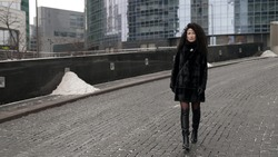 A curly-haired, stylish, middle-aged brunette woman in a black fur coat walks alone in the city on a cold day. Posing against the background of unusual buildings.