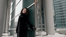 a curly-haired stylish middle-aged woman, a brunette in a black fur coat, walking alone in the city on a cold day, smiling. Posing near panoramic modern buildings.