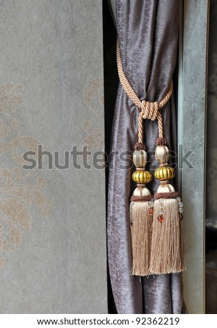 A curtain hold back by tassel