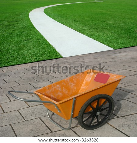 A curved concrete trail on a field of green grass,  orange cart.