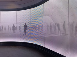 A curved led digital display screen wall. The wall is depicting moving shadows of people on a white background.