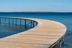 A curved wooden boardwalk leads out into the blue ocean
