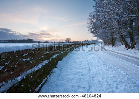 A curving snow-covered road running between a wall and woodland, with sunset sky in the background.