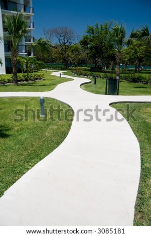 A curvy concrete path going through the grounds of a tourist resort