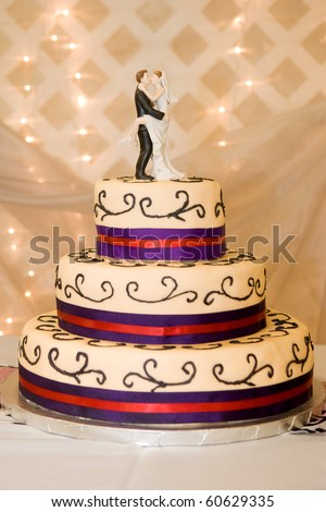 A custom wedding cake with a bride & groom decoration on top.