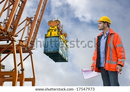 A Customs Control officer, checking the unloading of freight containers at an industrial harbor, wearing a hard hat and safety coat