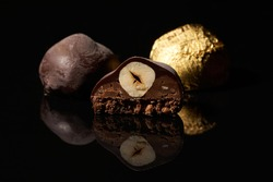 A cut chocolate candy with a nut and two whole candies, one of which is in a golden wrapper on a black background with reflection