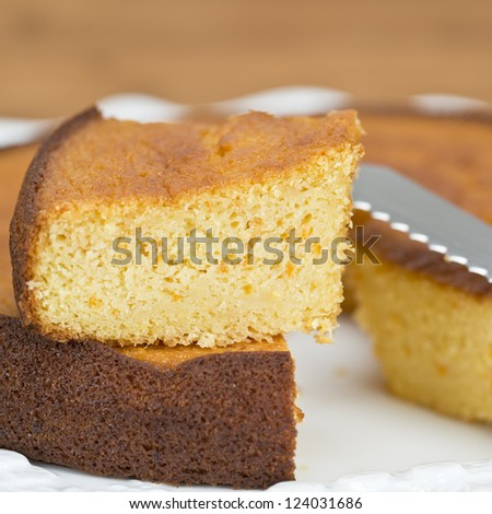 A cut homemade cake showing its texture on a wooden surface.