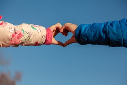 A cute abstract image showing the touching hands of a girl with pink coat and a boy with blue coat. Hands make heart shape against clear sky. A concept image for innocent love, valentines day, romance