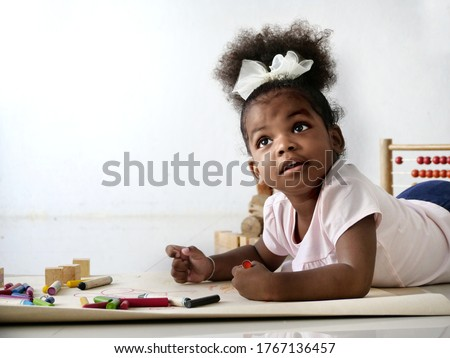 A Cute and adorable African girl lay down on the floor and drawing a picture with color pencil in the living room. Stay safe at home during the Covid-19 situation. A concept for education, learning.