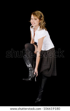 A cute and fresh-face young woman is removin her black patent leather boots.