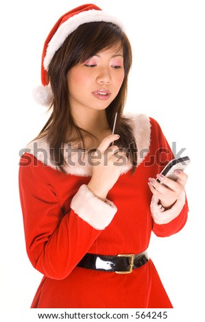A cute asian girl dressed as santa checks her list on a personal handheld computer