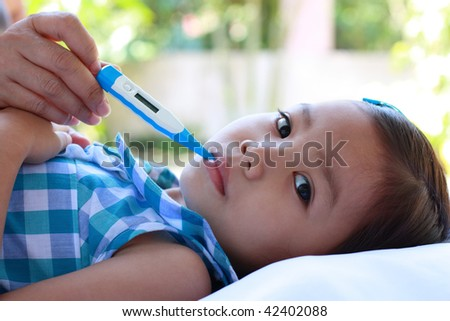 a cute asian girl with a fever and thermometer