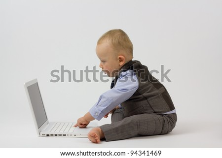 A cute baby boy is dressed in smart business clothes and is with his laptop ready for work. Studio shot Isolated on white.