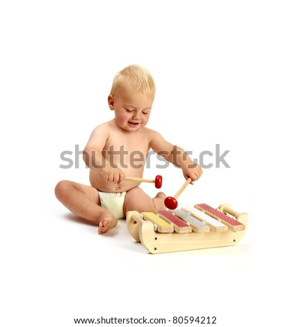 a cute baby boy playing a xylophone musical instrument isolated on a white background