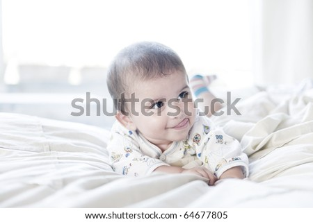 stock photo : A cute baby boy playing on the bed