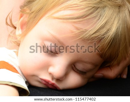 a cute baby boy sleeping in mother's arms