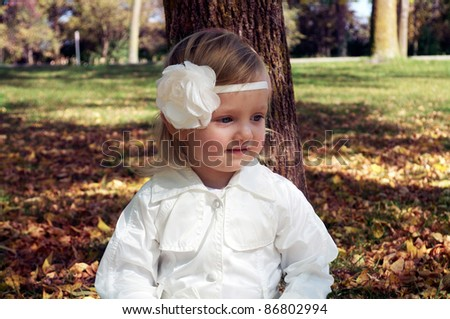 a cute baby girl in fall day