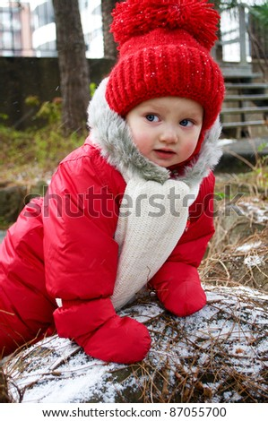 a cute baby girl in red snowsuit outside