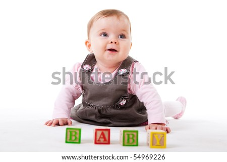 A cute baby girl is posing behind a set of children's blocks that spell out BABY.  Horizontal shot.