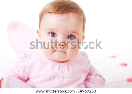 A cute baby girl wearing fairy wings stares wide-eyed at the camera.  Horizontal shot.