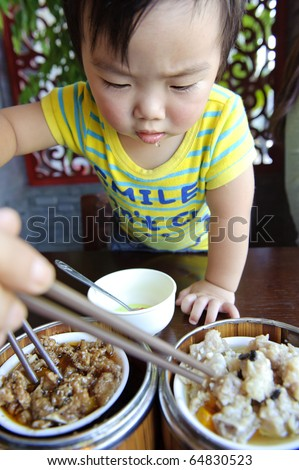 a cute baby is eating (The text on the clothes of baby : SMILE,Don't Cry)