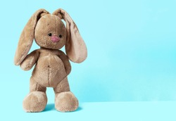 a cute baby soft toy bunny staying on a bright blue background