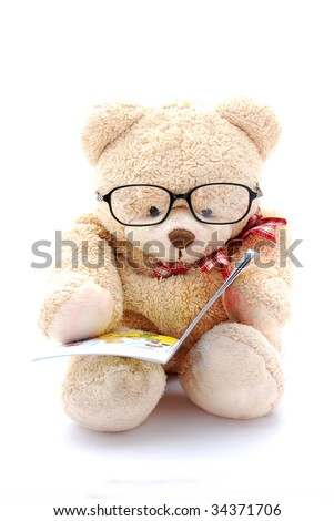 A cute beige teddy bear for kids to play with wearing eyeglasses, holding and reading a little book. Image isolated on white studio background.