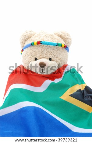 A cute beige teddy bear wearing a colorful Ndebele collar on the head and a South African flag. Image isolated on white studio background.