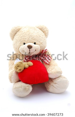 A cute beige teddy bear with smiling facial expression holding a big red Valentines Day heart. Image isolated on white studio background.