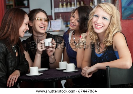 A cute blonde girl smiles while sitting with three friends in a cafe