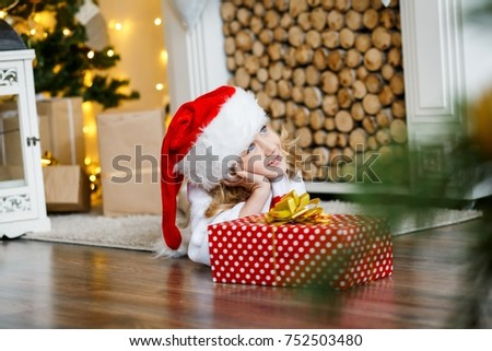 A cute boy in a red cap in front of the fur-tree and fireplace with candles and gifts unpacking presents. New year's eve. Christmas eve. Cozy holiday at the fir-tree with lights and gold decor. #752503480