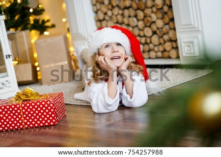 A cute boy in a red cap near the hristmas tree. New year's eve. Christmas eve. Cozy holiday at the fir-tree with lights and gold decor. #754257988