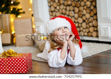 A cute boy in a red cap near the hristmas tree. New year's eve. Christmas eve. Cozy holiday at the fir-tree with lights and gold decor. #754257991