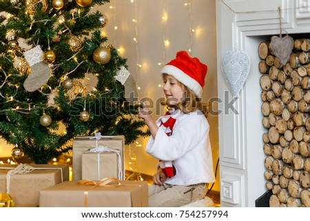 A cute boy in a red cap near the hristmas tree. New year's eve. Christmas eve. Cozy holiday at the fir-tree with lights and gold decor. #754257994