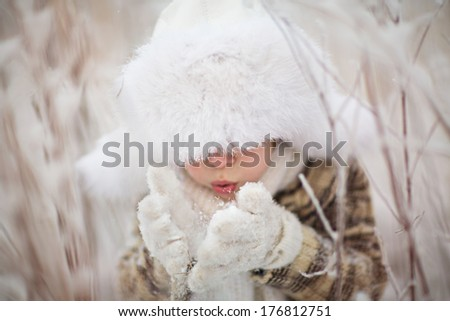 A cute boy in a white fur cap with ear-flaps blowing the snowflakes off his mittens on a frosty winter day